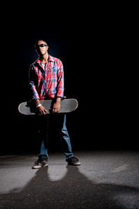 African American skateboarder wearing sunglasses holding his skateboard under dramatic lighting with dramatic shadows.
