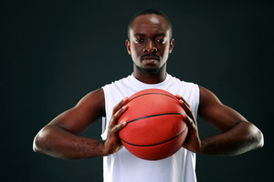 African man holding basketball ball over black background