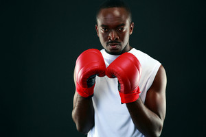 African man in boxing gloves standing over black background