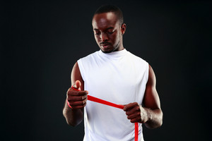 African man with tape measure over black background