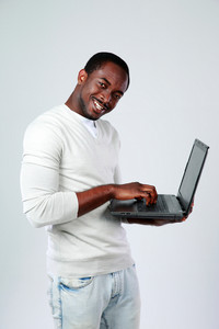 African man working on laptop while standing up on gray background