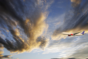 airliner flying through cloud-scapes, blue sky