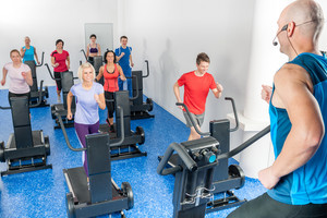 Alpinning class of young adults with fitness personal trainer
