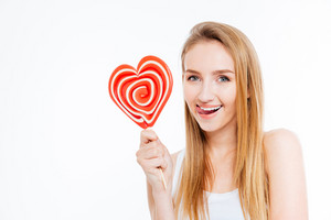 Amusing attractive young woman showing tongue and holding heart shaper lollipop over white background