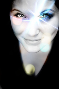 An abstract womans portrait with a glowing lens flare on her face.