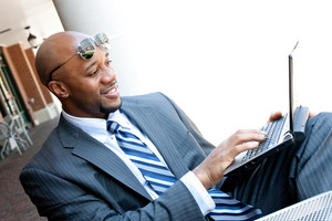 An African American business man in his early 30s using his laptop or netbook computer outdoors with copy space for your text.