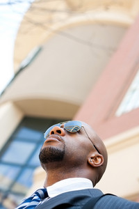 An African American business man wearing his sunglasses and business suit in the city with copy space.