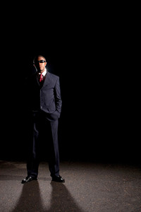 An African American man dressed in a dark colored suit and sunglasses standing in front of a dark black background.