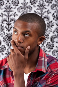 An African American man with his hand on his chin thinking deeply about something in front of a damask style background. Shallow depth of field.