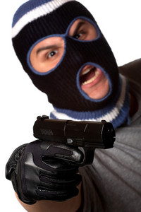 An angry looking man wearing a ski mask pointing a black handgun at the viewer. Shallow depth of field with sharpest focus on the gun.