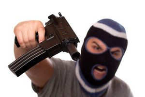An angry looking man wearing a ski mask pointis a black automatic machine gun at the viewer. Shallow depth of field with sharpest focus on the gun.