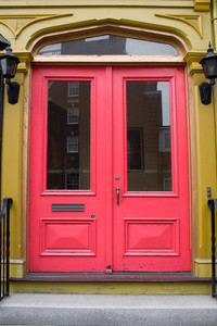 An antique doorway with red painted doors.