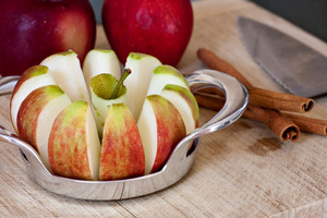 An apple sliced is into wedges and cored using a handy kitchen tool.