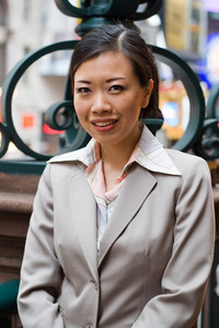 An Asian woman dressed in business attire in the city.