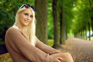 An attentive sexy young blonde woman in a tan jersey sits on a park bench looking upwards with empty tree lined avenue behind.