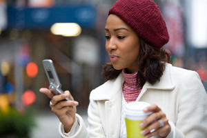 An attractive African American business woman checks her cell phone in the city. She could be text messaging or even browsing the web via wi-fi or 4G connection.