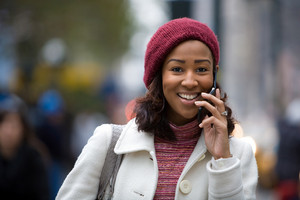 An attractive African American woman talking on her cell phone in the city.