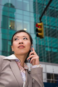 An attractive Asian business woman talking on her cell phone in the city.