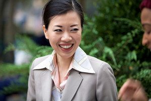 An attractive Asian woman dressed in business attire laughing at the words of her business associate.