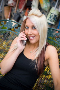 An attractive blond woman has a happy look on her face while talking on her cell phone.