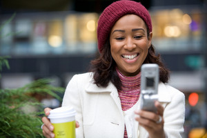 An attractive business woman checking her cell phone in the city.  She could be text messaging or even browsing the web via wi-fi or a 3g connection.