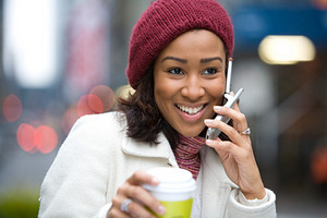 An attractive business woman talking on her cell phone along with a hot coffee.
