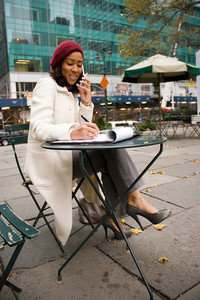 An attractive business woman talking on her cell phone while sitting at a table outdoors.