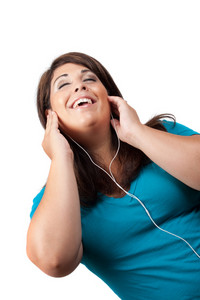 An attractive Hispanic woman listening to and getting into the music playing through her stereo earbud headphones.