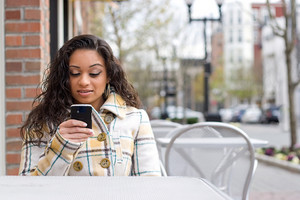 An attractive Indian woman texting or searching the web on her cell phone while seated at a table outdoors.