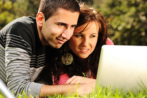 An attractive man and woman couple in the park on laptop computer