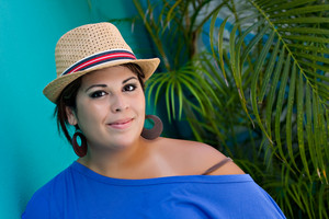 An attractive young Hispanic woman smiling with her hat and outdoors by some tropical foliage.