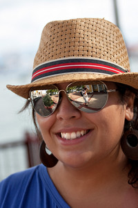 An attractive young Hispanic woman smiling with her hat and sunglasses on outdoors.
