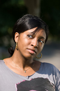 An attractive young Jamaican woman with a contemplative look on her face.