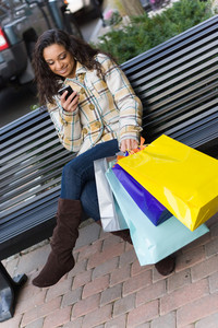 An attractive young woman checking her cell phone while out shopping in the city.  She might be texting or surfing the internet.
