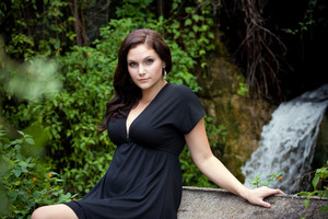 An attractive young woman wearing a black dress posing by a waterfall.