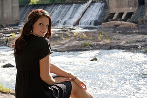An attractive young woman wearing a black dress sitting by a river.