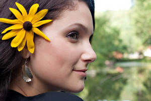 An attractive young woman wearing a black eyed susan wildflower in her hair.