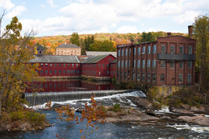 An Autumn river scene with some falls and old mill buildings alongside with colorful foliage on the horizon.