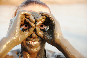 An elderly woman enjoying the natural mineral mud on face sourced from the dead sea in background