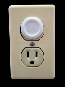 an electrical outlet complete with child safety plug - isolated over black