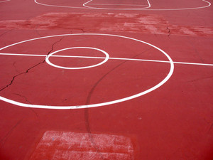 An empty basketball court with white painted lines.