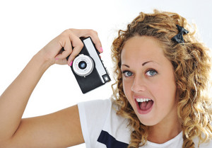 An excited young woman shouting holding a retro camera in hand