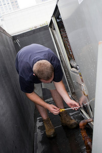 An HVAC heating ventilating air conditioning technician repairing or maintaining a large commercial unit.
