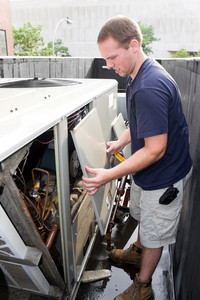 An HVAC heating ventilating air conditioning technician working on a large commercial unit.