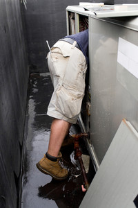 An HVAC technician repairing a commercial unit.