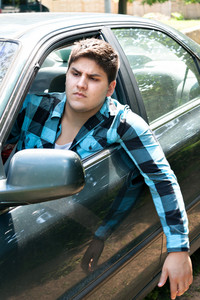 An irritated young man driving a vehicle with his head and arm hanging out of the window.