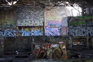 An old abandoned area that has been converted to a paint ball course. Every inch is covered with graffiti.  Focus is on the back wall.