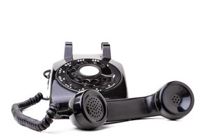 An old black vintage rotary style telephone off the hook isolated over a white background.