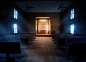 An old empty church with light rays coming through the windows