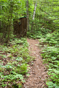 An old outhouse on the trail through the woods.